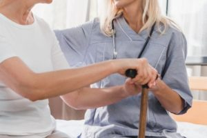 nurse-and-happy-senior-woman-with-cane-smiling-eac-C2ATQ3X (1)