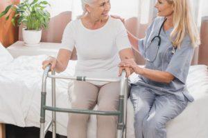 nurse-and-senior-woman-with-walker-smiling-each-ot-KBKP9EZ (1)